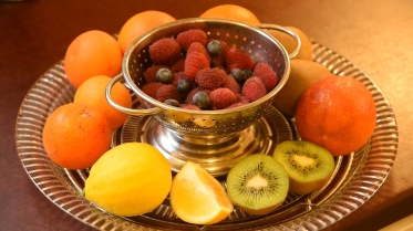 Fruit salad ingredients on a glass plate and colander