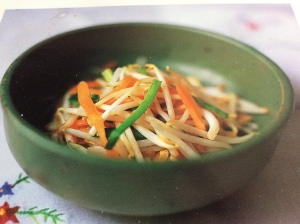 Asian bean sprout salad with carrots in a green bowl