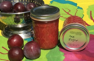 2 Jars of no-sugar plum jam and plums in a colander on a tablecloth
