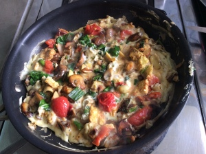 Eggs and fresh vegetables in a breakfast scramble including tomatoes, spinach, mushrooms and spring onions