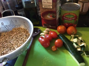 Lentils, tomatoes, onion, on cutting board to be made into Lentil soup