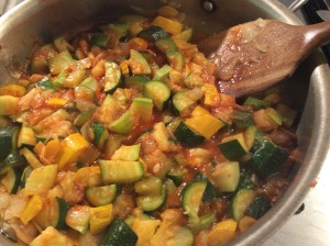 A mix of squash, onion and ketchup sautéed in pan