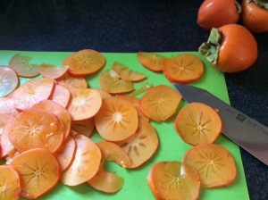 Sliced fresh persimmons on a green cutting surface