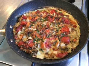 Egg and vegetable breakfast tortilla in pan
